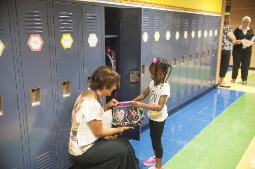 Ms. Farrington helps Nevesh Harris get something from her locker. | William Camargo/Staff Photographer