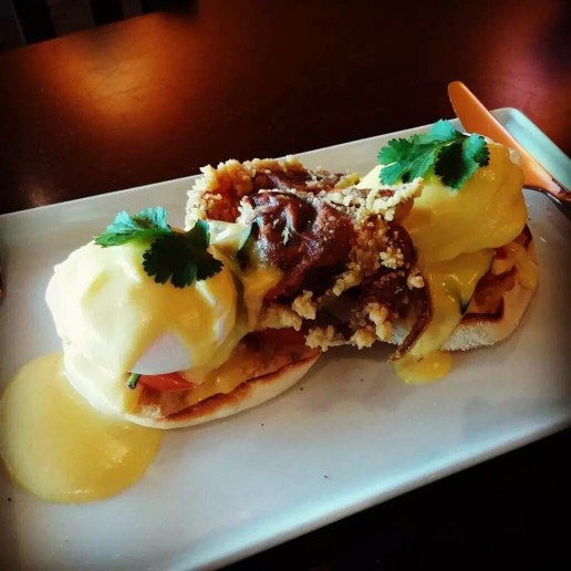 Soft shell crab eggs Benedict with avocado, basil, tomato layers, topped with yellow curry hollandaise sauce.