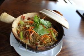 Shrimp in clay pot sizzles with bacon, shiitake mushrooms, shredded carrots, fresh cilantro.