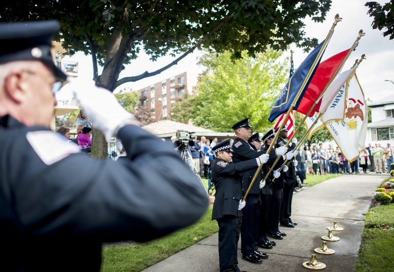 Police officers and firefighters get ready to plant flags during a memorial dedication for the officers and firefighter who lost their lives on duty. | William Camargo/Staff Photographer