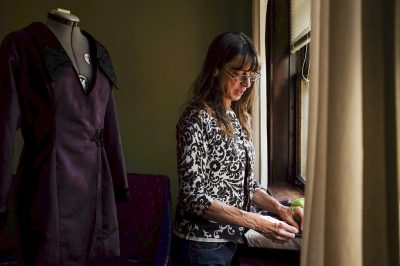 Lee Conte (above) works on her costume for this Sunday's cemetery walk. | William Camargo/Staff Photographer