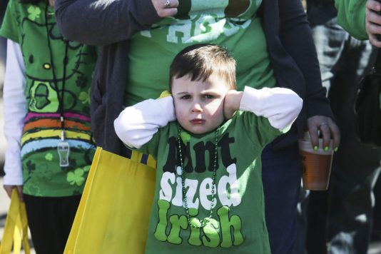 Vincent Niehus, 4, holds his ears as emergency vehicles cruise down Madison Street during the Forest Park St. Patrick's Day Parade on March 7. | File