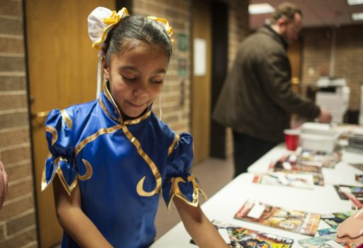 Jessica Flowers, dressed as Chun-Li, a Street Fighter video game character, picks out free comics. | William Camargo/Staff Photographer