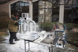 Hawk, an ice sculptor with Nadeau's Ice Sculptures, works on a carving with a small electronic chainsaw in front of the Forest Park Public Library for its centennial celebration. | William Camargo/Staff Photographer