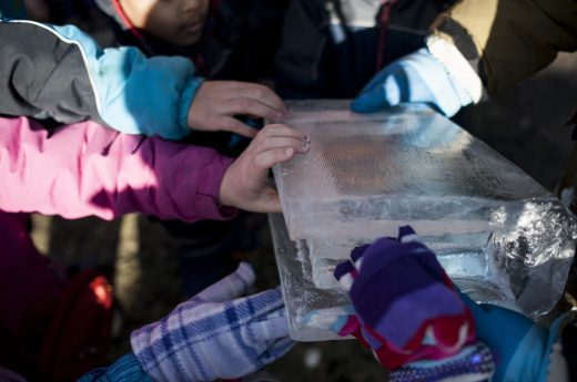 Children touch a piece of ice in the shape of a book. | William Camargo/Staff Photographer