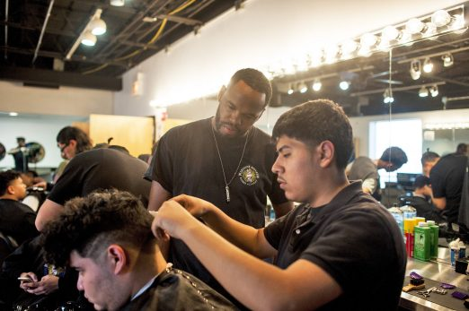 Eric Cisneros works on the hair of his classmate, Gerardo Salinas, while Erskine Reeves supervises during a Feb. 4 session of the Proviso East High School barber training program. Reeves teaches students from both Proviso East and West skills that earn them a barber's certificate. | William Camargo/Staff Photographer