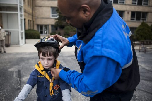 Locklin Bell, 7, gets his helmet fixed by Officer Kendall. | William Camargo/Staff Photographer