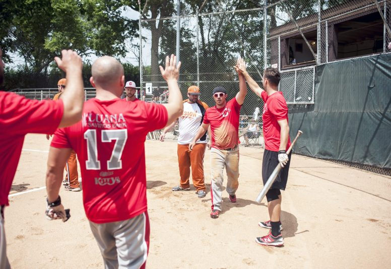 TJ Cataldo of Chuck's high-fives his teammates after scoring a run during a game against Vision at the No Gloves National Tournament in Forest Park last Saturday. | William Camargo/Staff Photographer