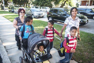 Nilai and Gumy Nandhan catch their friend Daniel Ingram walking to their first day of kindergarten at Garfield Elementary School in Forest Park on August 22. | William Camargo/Staff Photographer