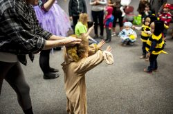 A small lion gets an assist interacting during storytime. | William Camargo/Staff Photographer