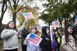 Children from Garfield Elementary raise their American flags. | William Camargo/Staff Photographer
