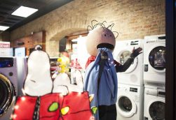 The Forest Park Review's Joyce Minich, dressed as Linus, reacts to the crowd in the Grand Appliance window during the Holiday Walk on Friday night. Snoopy slept through it all. | William Camargo/Staff Photographer