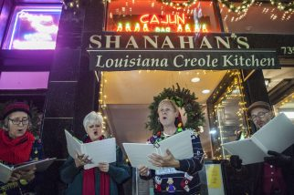 Singers carol in front of Shanahan's in downtown Forest Park during the annual Holiday Walk & Festival of Windows on Friday. | William Camargo/Staff Photographer