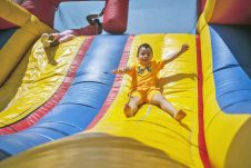 Johnathan Velez slides down a inflatable playhouse during the All School Picnic at The Park on May 19.   File photo