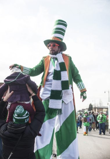 Forest Park's tallest leprechaun greets one of the many young spectators during Forest Park's St. Patrick's Parade on Madison Street last Saturday.   William Camargo/Staff Photographer