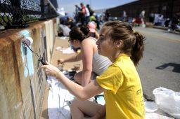 Katie Bartlett covers the rust along with other artists during the public painting event on Circle Bridge last weekend. | William Camargo/Staff Photographer