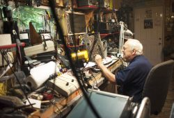 Ed Huther repairs a radio in his garage on June 30. After retiring, he turned his garage into a work station to fix analog radios for which there is still a demand.   William Camargo/Staff Photographer