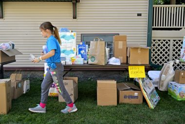 Storey Novak, 10, of Forest Park, looks for space to put donated items.   Alexa Rogals/Staff Photographer
