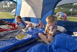 Cousins April Poleski, 6, left, and Caroline Cides, 5, eat dinner inside of their tent. | Alexa Rogals/Staff Photographer