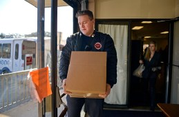 Firefighter Yvan Wojtecki carries a box of food out to a car. | Alexa Rogals/Staff Photographer