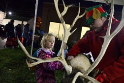 Kevin Anderson, right, shows Isabella Kochevar, 5, of Oak Park, how to pet the one of the reindeer, also known as caribou, on Dec. 1, during the annual Holiday Walk and Festival of Windows on Madison Street in downtown Forest Park. | Alexa Rogals/Staff Photographer