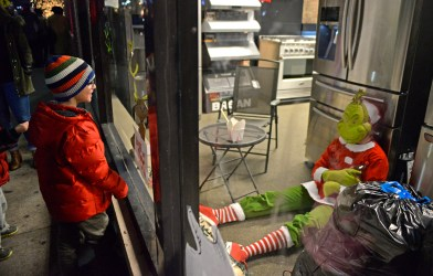 Participants walk past Grand Appliance and TV and look at the Forest Park Review's window display. | Alexa Rogals/Staff Photographer