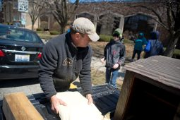 Tom Kunkel, founder of Urban Pioneer Group, helps the boy scouts carry tools to the spot where the mini food pantry will go. | Alexa Rogals/Staff Photographer