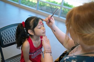 Maria Espana, of Forest Park, gets her face painted by Brittany Thurman. | Alexa Rogals/Staff Photographer