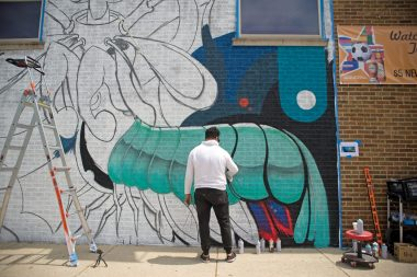 Artist Anthony Lewellen, of Chicago, works on a mural he is spray painting for the Shedd Aquarium on Friday, June 1, outside of Healy's Westside on Madison Street in Forest Park. | Alexa Rogals/Staff Photographer