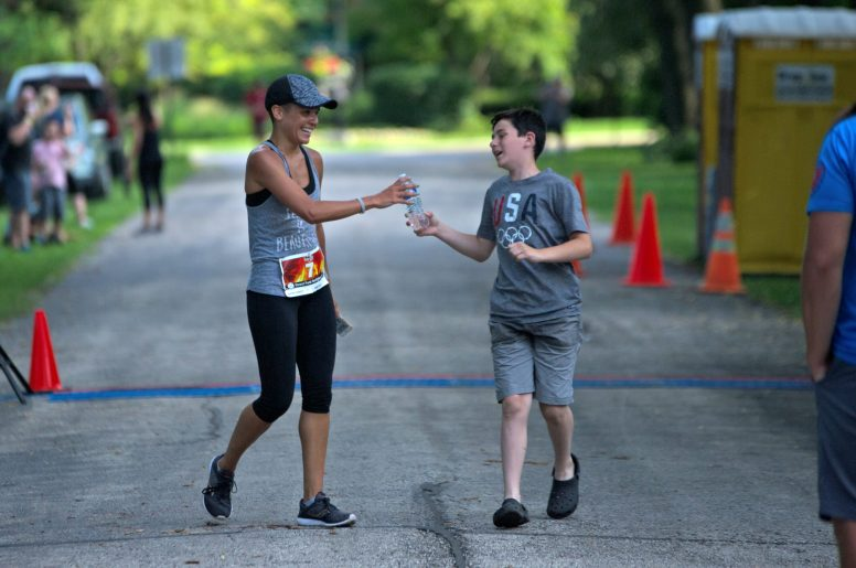 First place Melissa Connelly grabs a bottle of water during the annual Forest Park Firefighters 5K at Concordia Cemetery in Forest Park.   Alexa Rogals/Staff Photographer