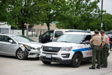 The damaged silver Hyundai Sonata is seen blocked in by several police vehicles on Wednesday, Aug. 29, 2018, in the parking lot at the United States Postal Service building on Garfield Street near Harlem Avenue in Oak Park, Ill. (ALEXA ROGALS/ Staff Photographer)
