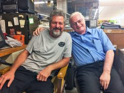 Son Mike and father Ed Nutley relax in their back office which is papered with photos of their family. | Submitted photo