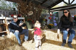 Melissa and Ryan Orr, of Forest Park, play with their daughter, Madelyn, 2, in the hay.   Sarah Minor/Contributor