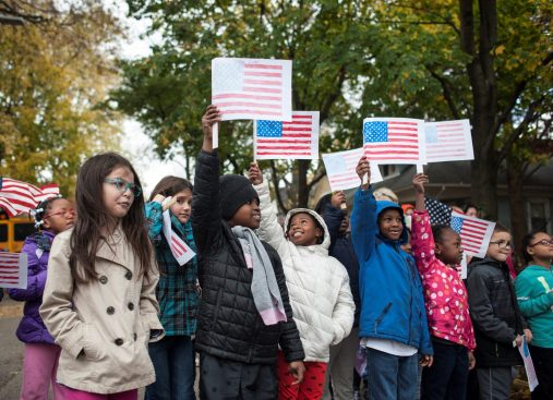 Children from Garfield Elementary raise their colored American flags during the annual Veteran Day's event in Forest Park on November 11, 2016.