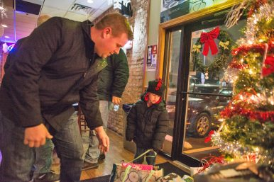 Jeff Aschenbach, left and his son, Andrew Aschenbach put gifts under the tree during Mayor Calderone's Annual Community Toy Drive at R Place on Harlem Avenue in Forest Park. | Alexa Rogals/Staff Photographer