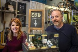 Owners Melody Kratz, left, and Bryan Shamhart stand next to the glass display holding their different CBD products including oils, gummies and lotions at Studio 8 in Forest Park. | Alexa Rogals/Staff Photographer