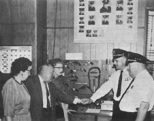"""June 4, 1964 the Forest Park Review highlighted some of the open houses and tours that had taken place during the """"Clean up, paint up, fix up"""" week. Here, Chief Elmer Schnurstein watches Lt. Ed Ziebell demonstrate a handcuff device to a visitor."""