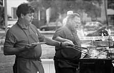 Bob Collins and Mark Dwyer, volunteering for Forest Park Youth Soccer, grill up burgers for a hungry crowd.