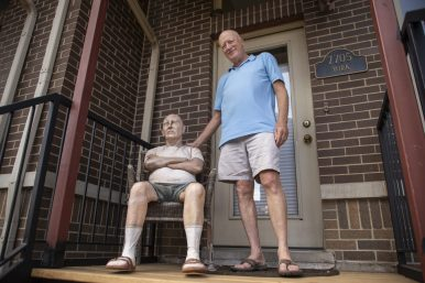 Rich White, sits down in front of a life-sized sculpture of himself on the front porch of York Street in Forest Park. | Alexa Rogals/Staff Photographer