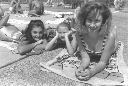 Shannon Collins (right) and her friends Lidia and Tihana Ilic work on their tans at the Forest Park Pool on a Friday afternoon.
