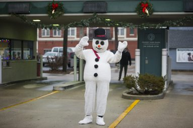 Frosty the Snowman waves to visitors on Saturday, Dec. 12, 2020, during a drive-thru Santa event at the Forest Park Bank on Madison Street in Forest Park, Ill. | ALEX ROGALS/Staff Photographer