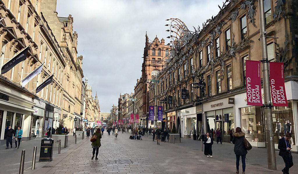 Pedestrians walk past high street shops Buchanan Street in Glasgow