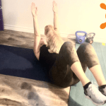woman lies on an exercise mat doing a workout and there's a small dog sitting on her chest