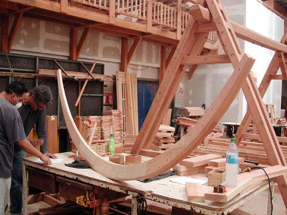 In this photo, our in-house master carpenter, Tony Toledo and I are working out ways of strengthening and refining the basic skeleton of an arched hammock stand design (the basic skeleton is next to us on the table).