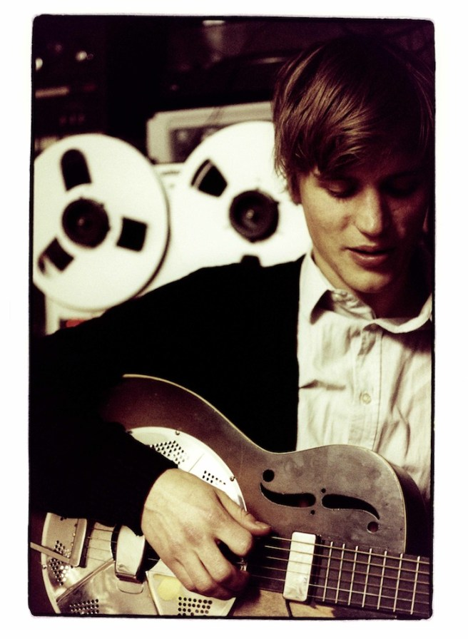 Johnny Flynn, playing the guitar in a studio
