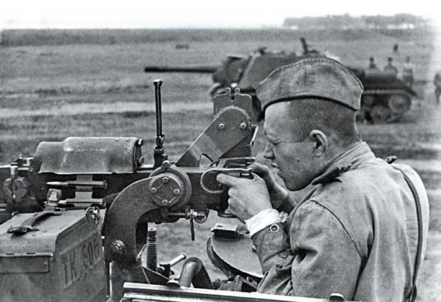 Soviet tanker firing a DShK heavy machine gun from an ISU-152 tank destroyer.
