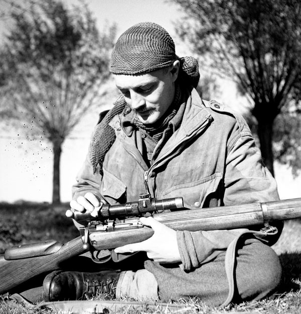 Sergeant H.A. Marshall of The Calgary Highlanders cleans the telescopic sight of his No.4, MkI(T) rifle