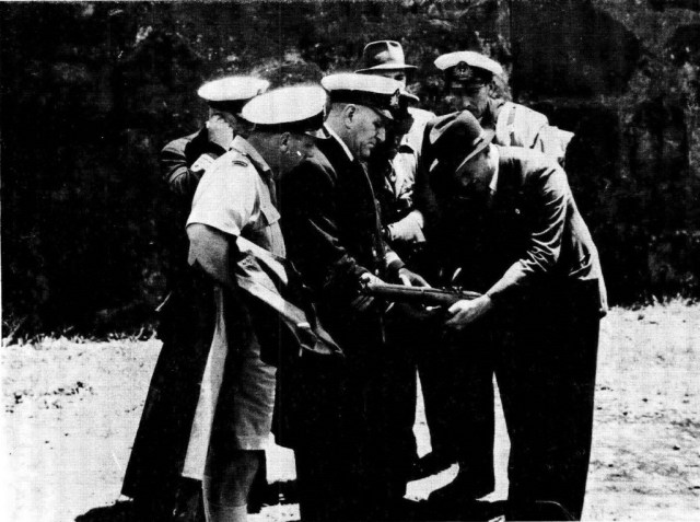 Mr Rieder shows his invention to Royal Naval officers, an army officer and a civilian after a demonstration outside the Castle in Cape Town