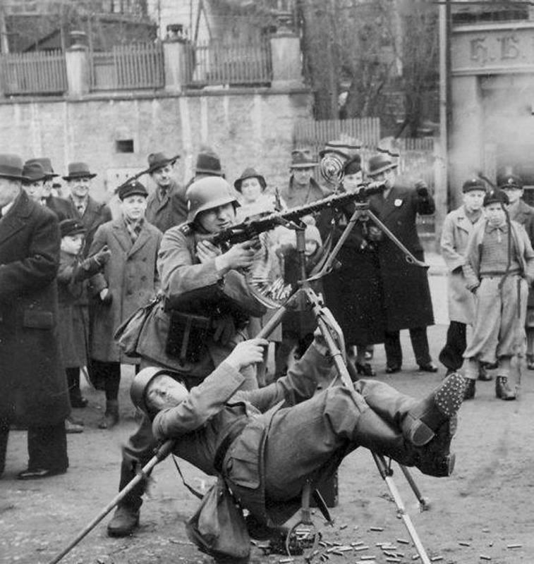 German soldier using his body weight to stabilize an antiircraft machine gun mount