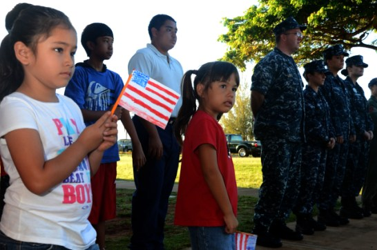 Students from St. Theresa's Catholic School wave American Flags during a ceremony honoring veterans. Sailors assigned to the Pacific Missile Range Facility also participated in the Veterans Day Ceremony.
